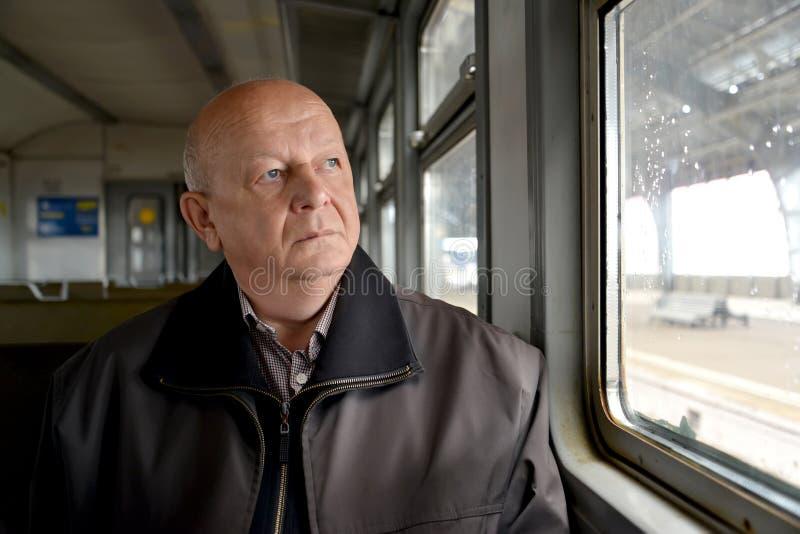 Starsi mężczyzna zamyślenia spojrzenia z elektrycznego pociągu wygrywają zdjęcia stock