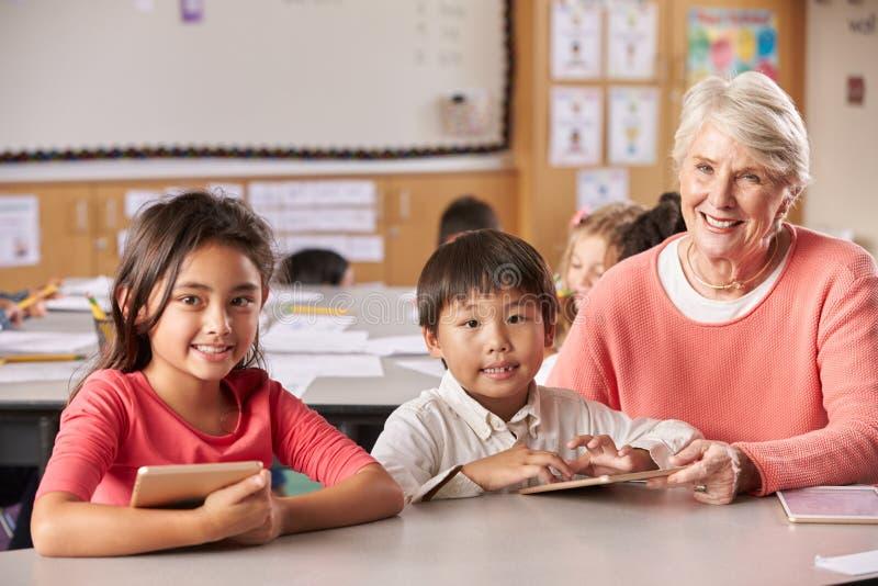 Starsi nauczyciela i szkoły podstawowej ucznie w sala lekcyjnej zdjęcie stock