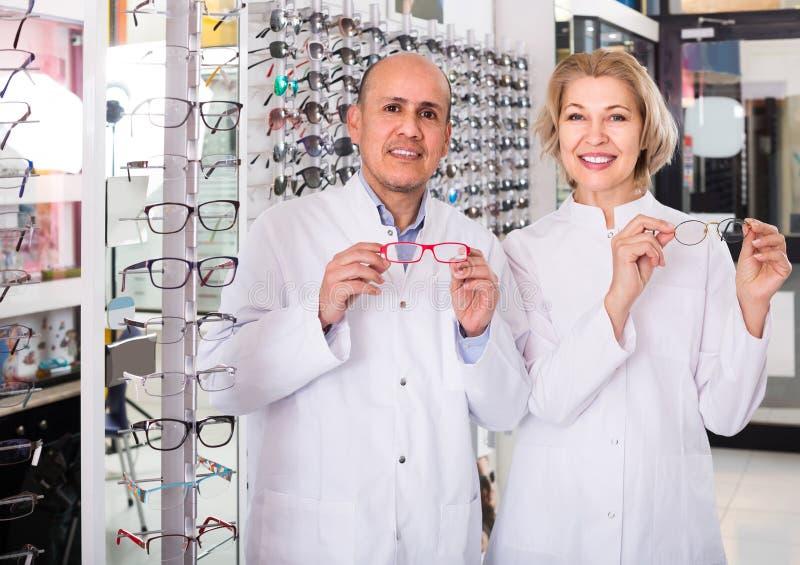 Starsi okuliści pomaga wybierać szkła w nowożytnym optyki sto zdjęcie royalty free