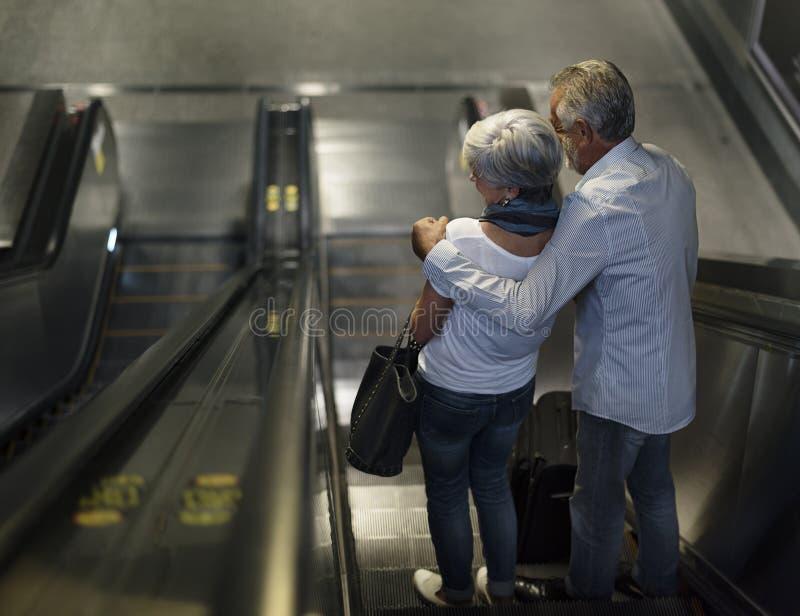 Starsi para turyści przy eskalatoru iść puszkiem fotografia stock