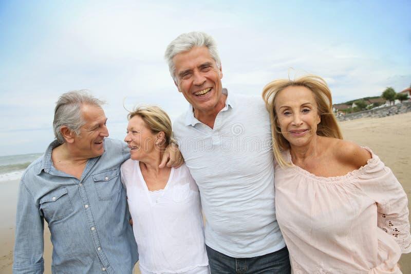 Starsi szczęśliwi ludzie chodzi na piaskowatej plaży obraz stock