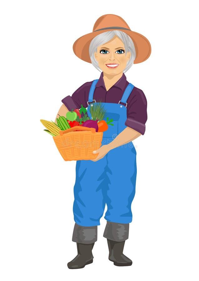 Starsza żeńska ogrodniczka jest ubranym kombinezony trzyma kosz świezi warzywa royalty ilustracja
