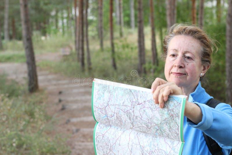 Starsza żeńska patrzeje mapy i planowania wycieczka dostaje przegraną w ciemnych drewnach lub zdjęcie stock