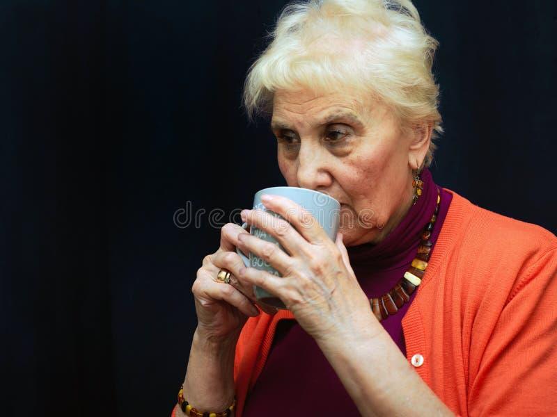 Starsza żeńska pije kawa zdjęcia stock