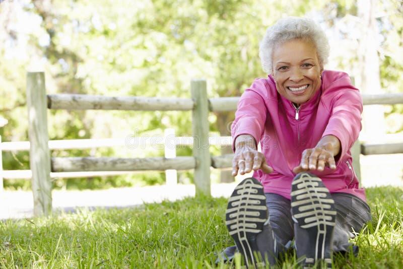 Starsza amerykanin afrykańskiego pochodzenia kobieta Ćwiczy W parku obraz royalty free