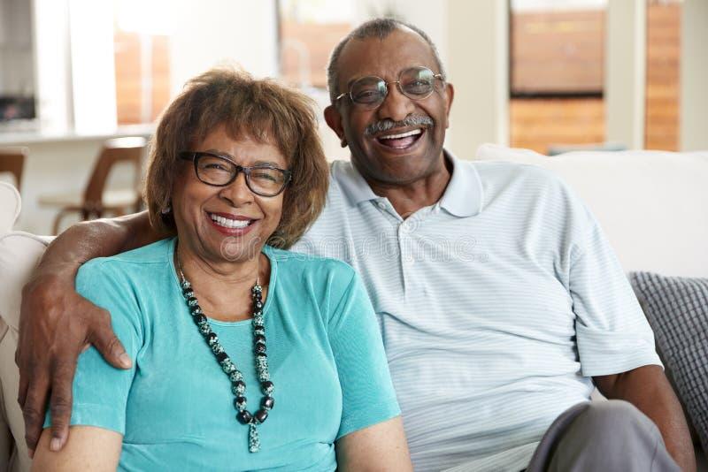 Starsza amerykanin afrykańskiego pochodzenia para siedzi w domu, ono uśmiecha się kamera, zakończenie w górę obraz royalty free