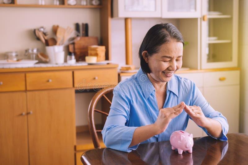 Starsza azjatka kobieta przykrywa dłoń nad skarbonką na emeryturę,Koncepcja oszczędzania pieniędzy fotografia stock