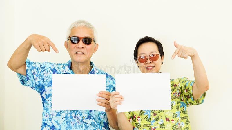 Starsza Azjatycka para jest ubranym wakacyjnego Hawaii koszulowego mienia biały s zdjęcie royalty free