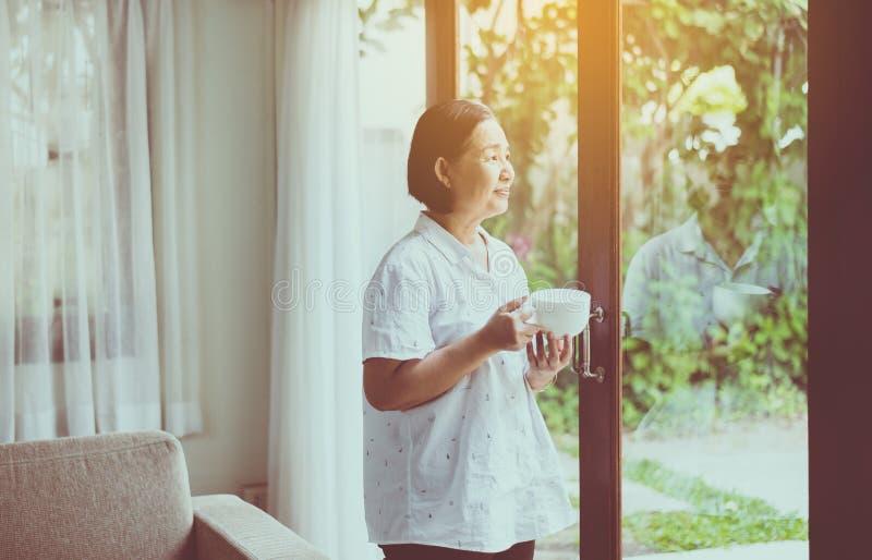 Starsza azjatykcia kobieta trzyma filiżanka kawy blisko okno w ranku zdjęcia stock