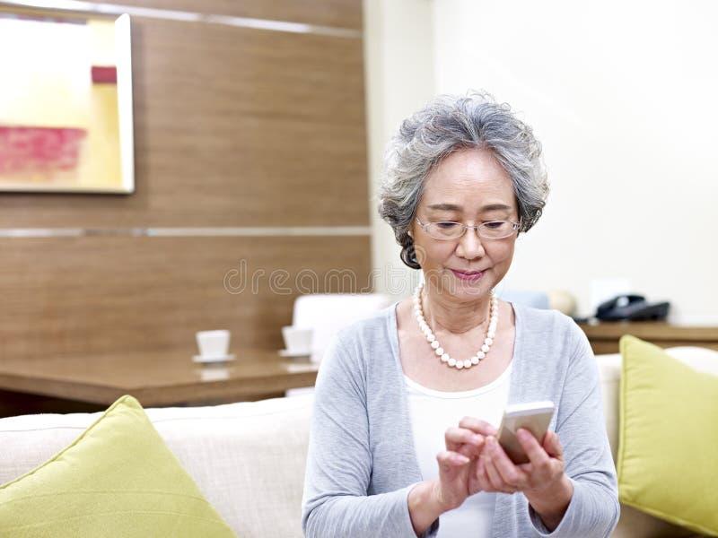 Starsza azjatykcia kobieta używa telefon komórkowego zdjęcie royalty free
