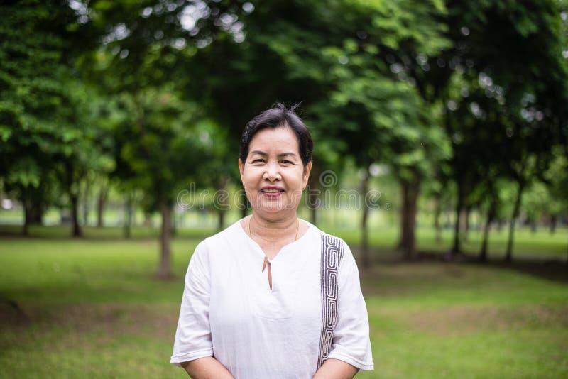 Starsza azjatykcia kobiety pozycja i przyglądająca kamera przy parka, Szczęśliwej i uśmiechniętej twarzą, obraz stock