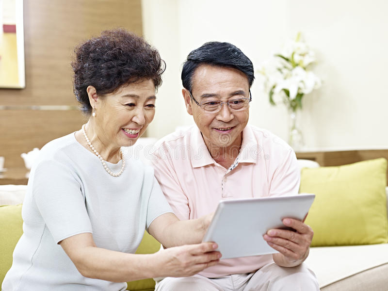 Starsza azjatykcia para używa pastylka komputer wpólnie obraz royalty free