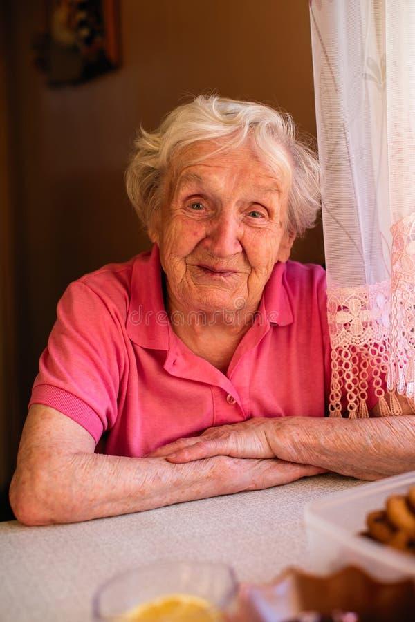 Starsza babcia pije herbaty w jej domu zdjęcia royalty free