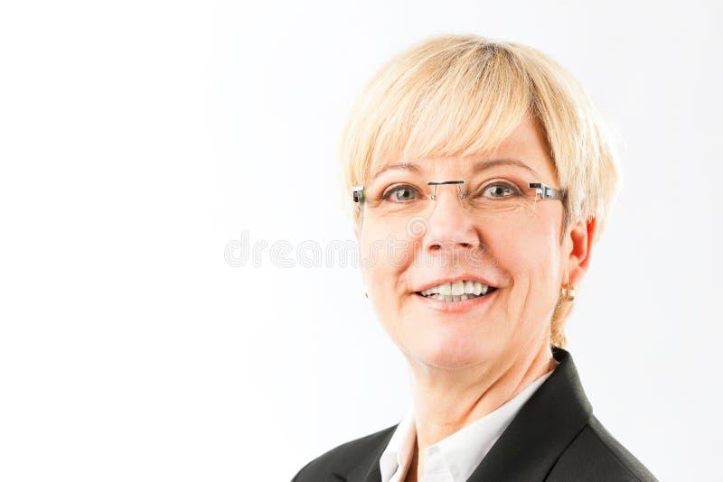Starsza biznesowa kobieta ono uśmiecha się będący ubranym eyeglasses obraz royalty free