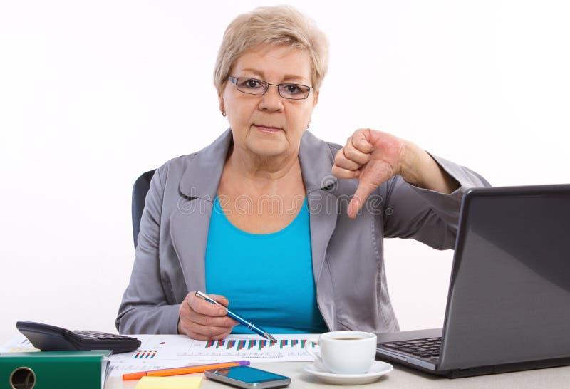 Starsza biznesowa kobieta pokazuje kciuki i pracuje przy jej biurkiem w biurze zestrzela, biznesowy pojęcie zdjęcie stock