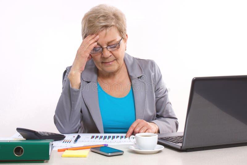 Starsza biznesowej kobiety mienia ręka na jej głowie działaniu przy jej biurkiem w biurze i, biznesowy pojęcie zdjęcia royalty free