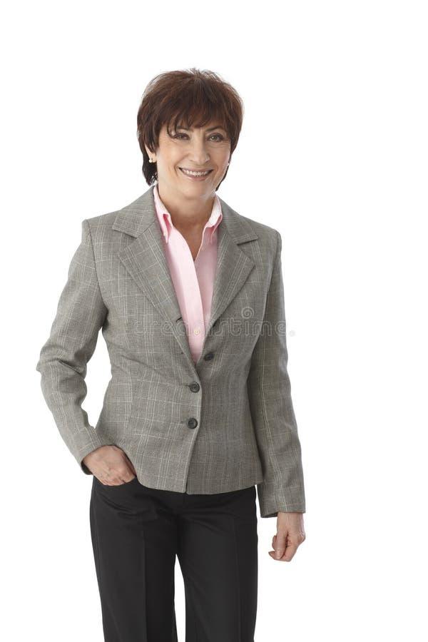 Starsza bizneswoman pozycja z ręką w kieszeni fotografia stock