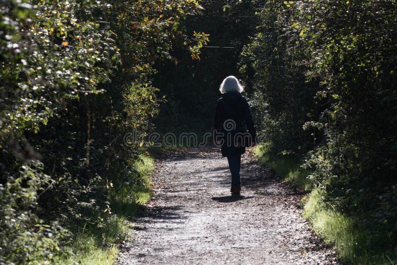 Starsza blondynki kobieta chodzi samotnie obrazy royalty free