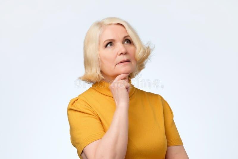 Starsza blondynki kobieta przyglądająca w górę i myśleć obrazy royalty free