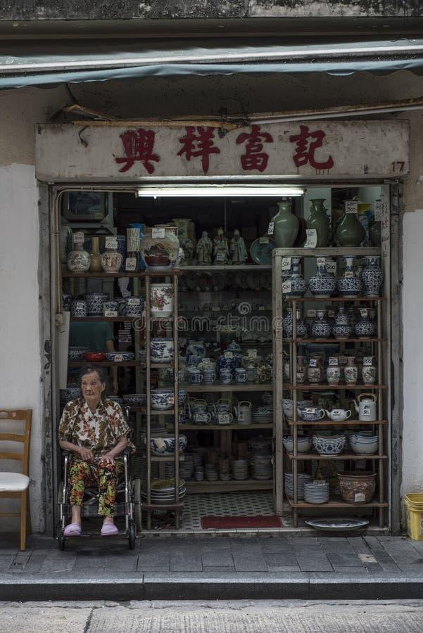 Starsza Chińska kobieta siedzi rodzinnym ceramics sklepem w Hong Kong obraz stock