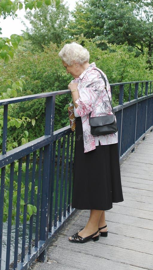 Starsza dama patrzeje w rzekę zdjęcie royalty free