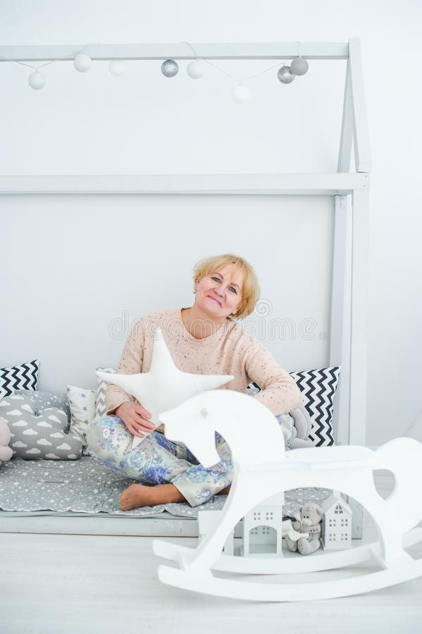 Starsza dama z gwiazdowym siedzącym pobliskim zabawkarskim koniem w białej sypialni Śmieszna starsza kobieta zdjęcia stock