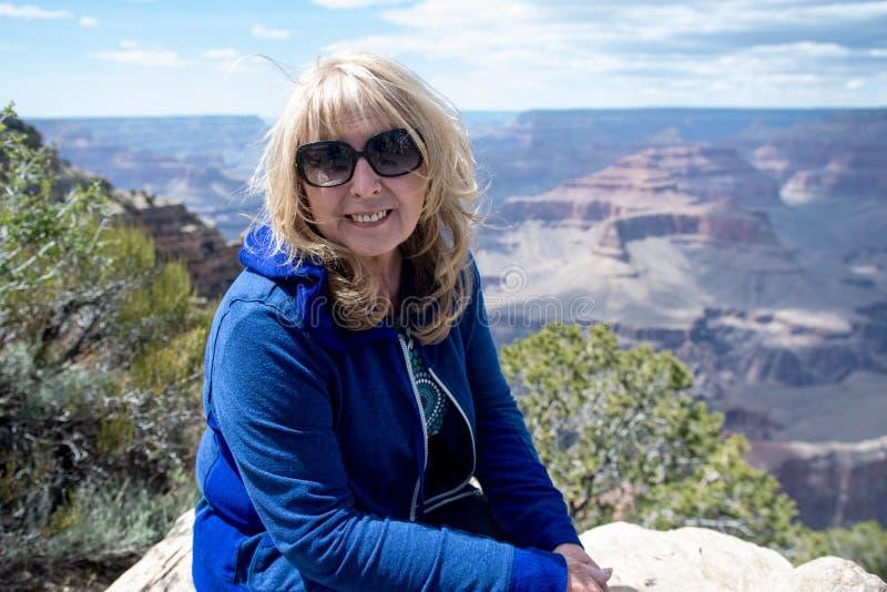 Starsza dorosła kobieta 60s siedzi przy punkt widzenia wzdłuż Południowego obręcza Grand Canyon park narodowy i pozy podczas gdy  zdjęcia stock