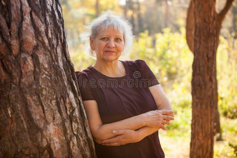 Starsza dorosła kobieta uśmiecha się do kamery latem w parku obrazy royalty free