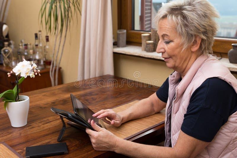Starsza dorosła kobieta z pastylką obraz royalty free