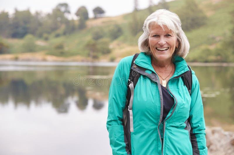 Starsza Kaukaska kobiety pozycja na brzeg jezioro ono uśmiecha się kamera, portret zdjęcie royalty free