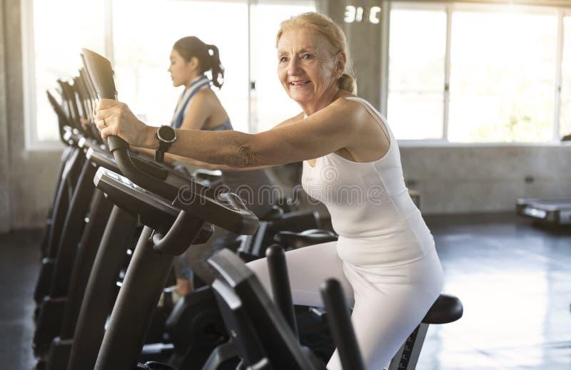 Starsza kobieta ćwiczy przędzalnianego rower w sprawności fizycznej gym elderly fotografia royalty free