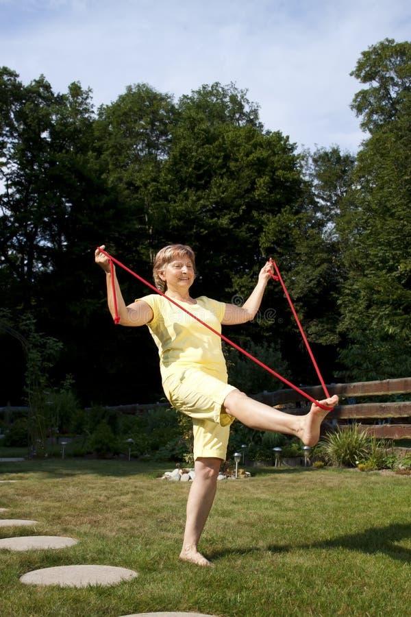 Starsza kobieta ćwiczy w ogródzie obraz stock