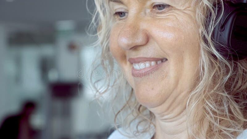Starsza kobieta angażuje na karuzeli w gym blond kobieta słucha muzyka z hełmofonami na karuzeli zako?czenie zdjęcia stock
