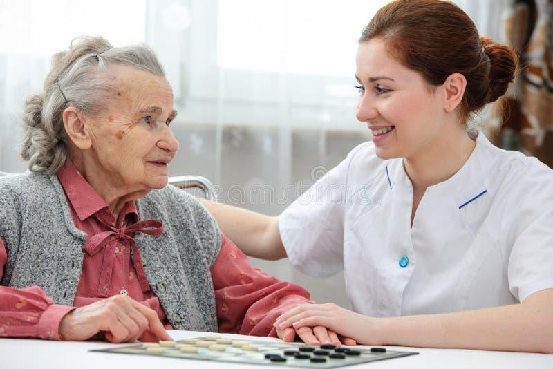 Starsza kobieta bawić się warcabów zdjęcie royalty free