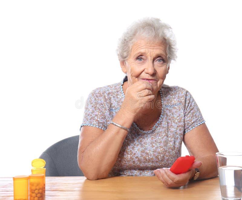 Starsza kobieta bierze pigułki podczas gdy siedzący przy stołem przeciw białemu tłu obraz royalty free