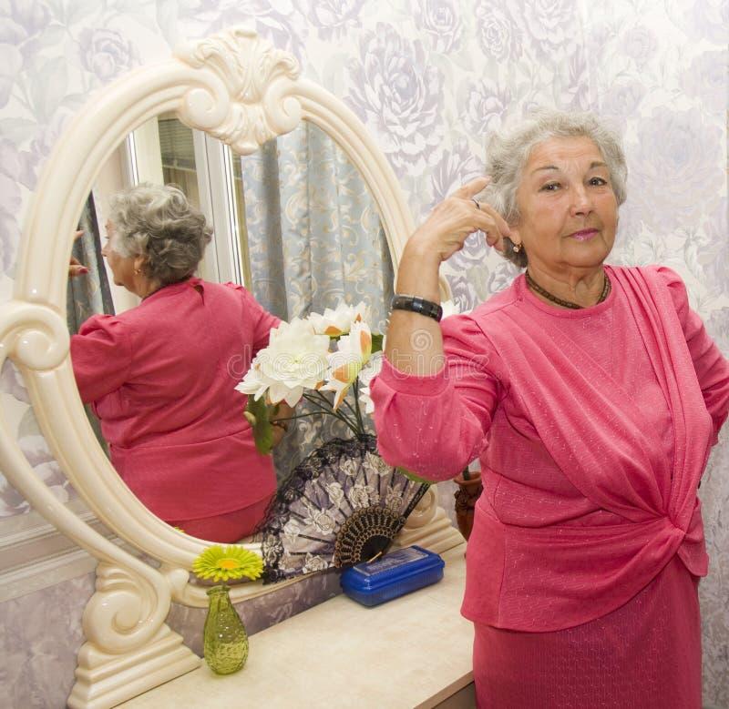Starsza kobieta blisko odzwierciedla obraz royalty free
