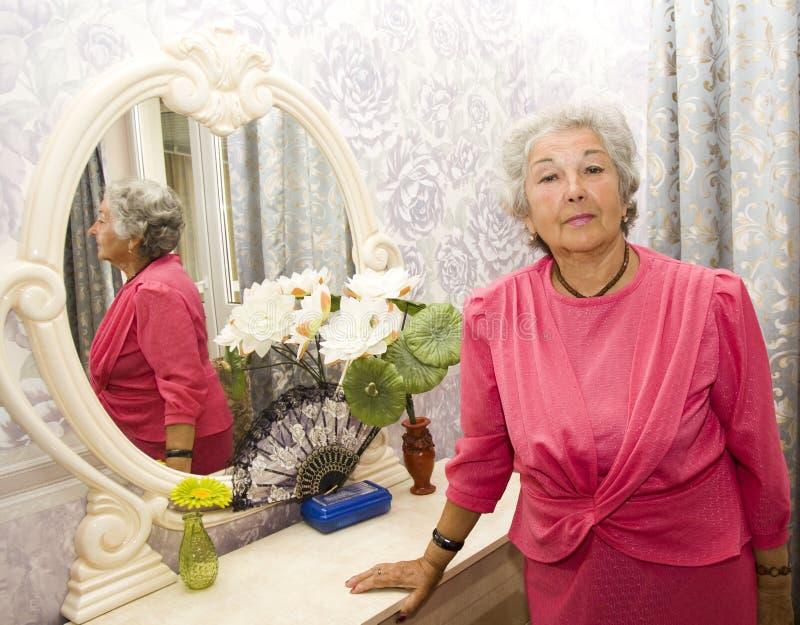 Starsza kobieta blisko odzwierciedla zdjęcia stock