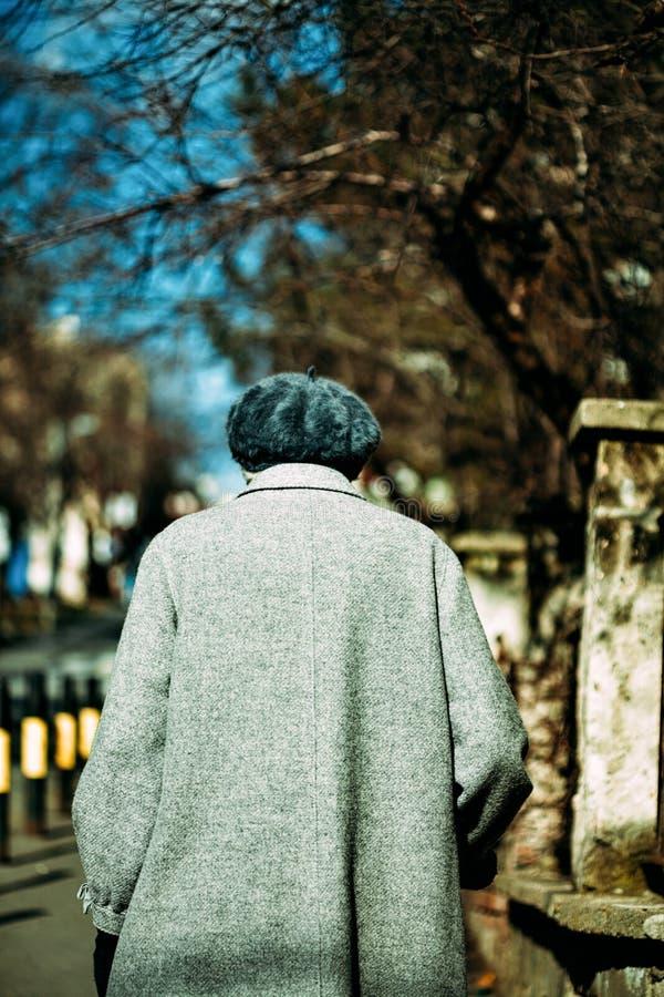 Starsza kobieta chodzi samotnie na ulicie zdjęcie stock