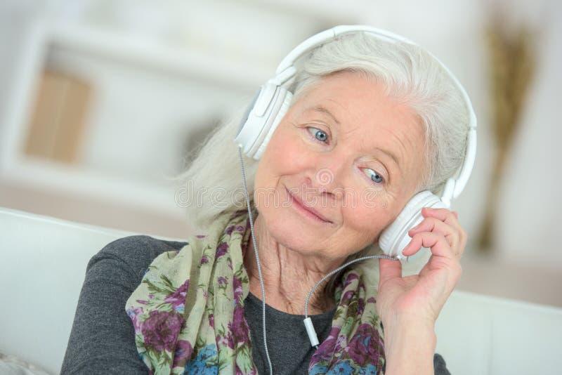 Starsza kobieta cieszy się muzykę w żywym pokoju zdjęcie royalty free