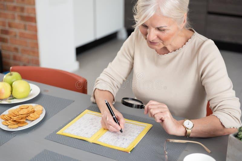 Starsza kobieta cieszy si? rozwi?zuj?cy crossword ?amig??wk? fotografia stock