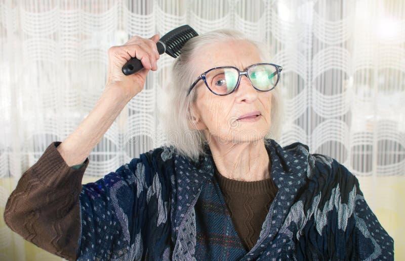 Starsza kobieta czesze jej włosy zdjęcie royalty free