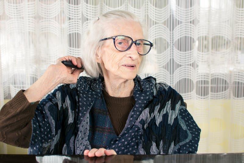 Starsza kobieta czesze jej włosy fotografia royalty free