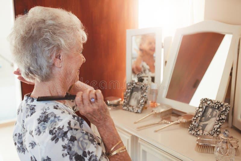 Starsza kobieta czesze jej włosy przy dresser w domu zdjęcia royalty free