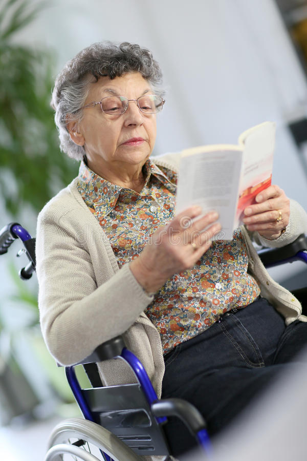 Starsza kobieta czyta książkę w wózku inwalidzkim fotografia stock