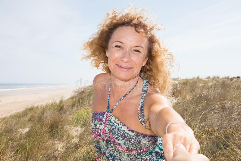Starsza starsza kobieta daje ręce mężczyzna kochanek na piasek plaży zdjęcia royalty free