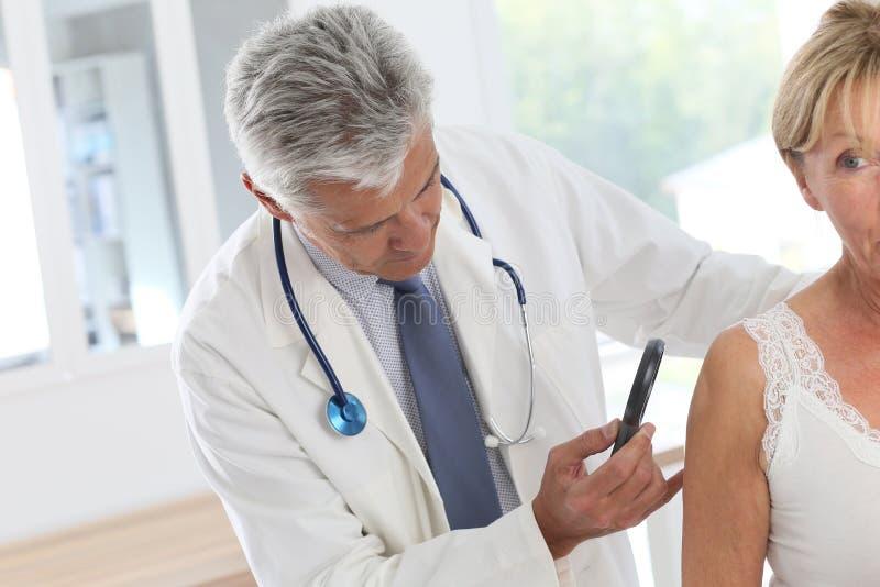 Starsza kobieta dostaje badania kontrolne przy dermatologiem obraz royalty free