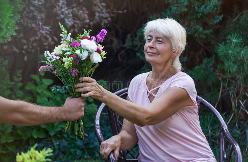 Starsza kobieta dostaje pięknego bukiet śródpolni kwiaty obrazy royalty free