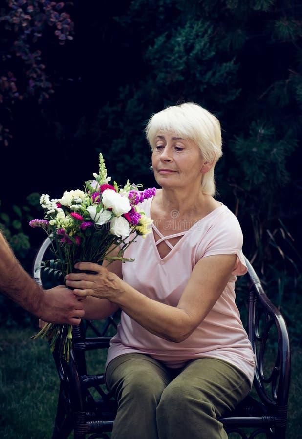 Starsza kobieta dostaje pięknego bukiet śródpolni kwiaty obrazy stock
