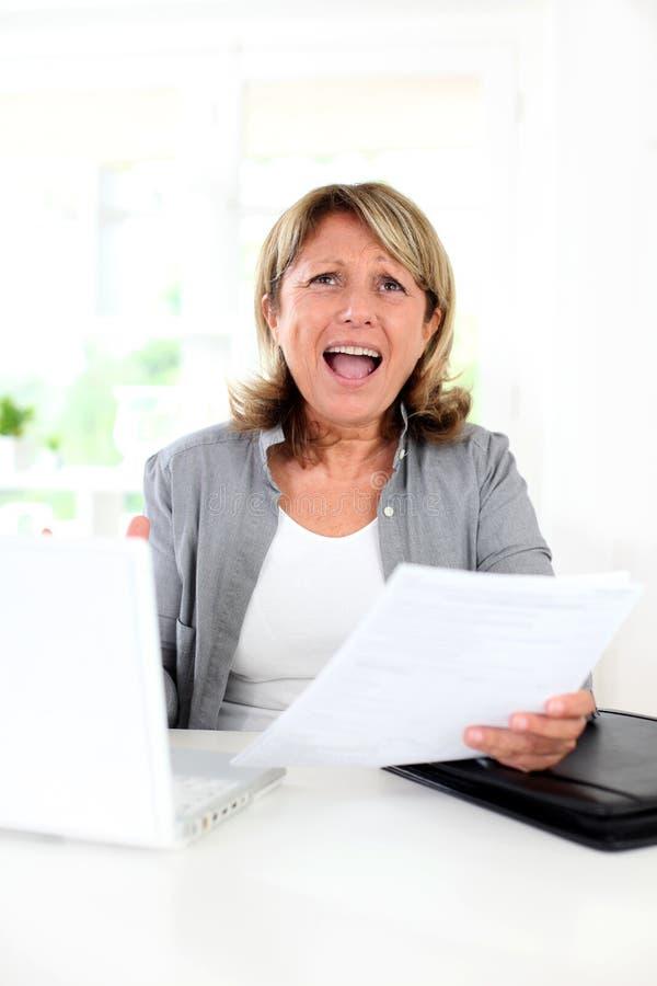 Starsza kobieta dostaje szalony przed laptopem fotografia royalty free