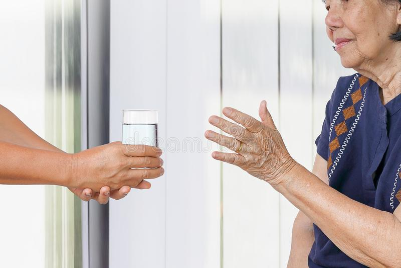 Starsza kobieta dostaje szkło woda od opiekunu fotografia royalty free